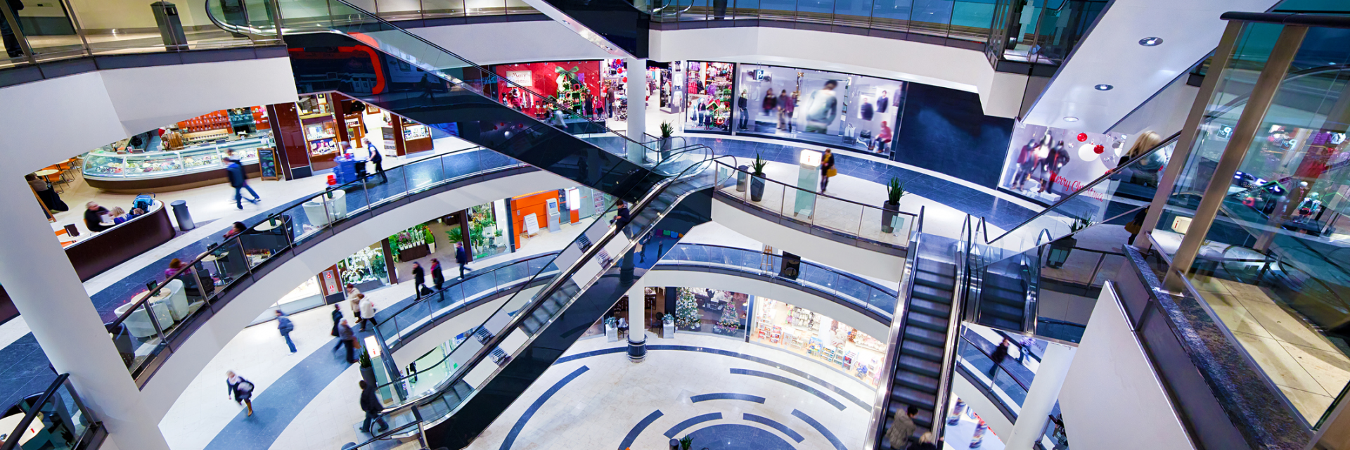 Modern, multi-level shopping mall interior. Busy sale time.