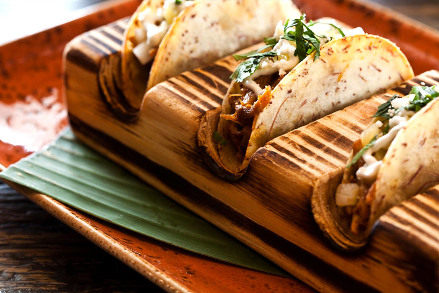 Focus on three gourmet Churrascos tacos, in a wooden taco holder, on a rust-colored clay dish.