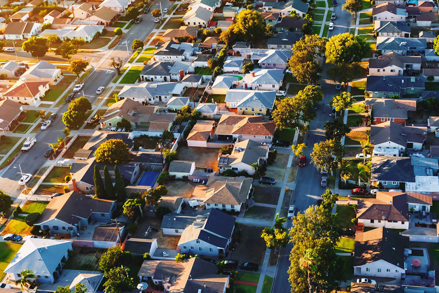 Residential neighborhood aerial featuring green lawns and trees at sunset.