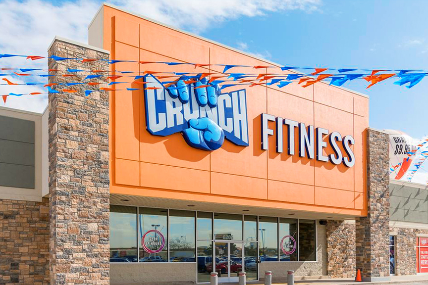 Orange and blue Crunch Fitness signage and building exterior against a blue sky.