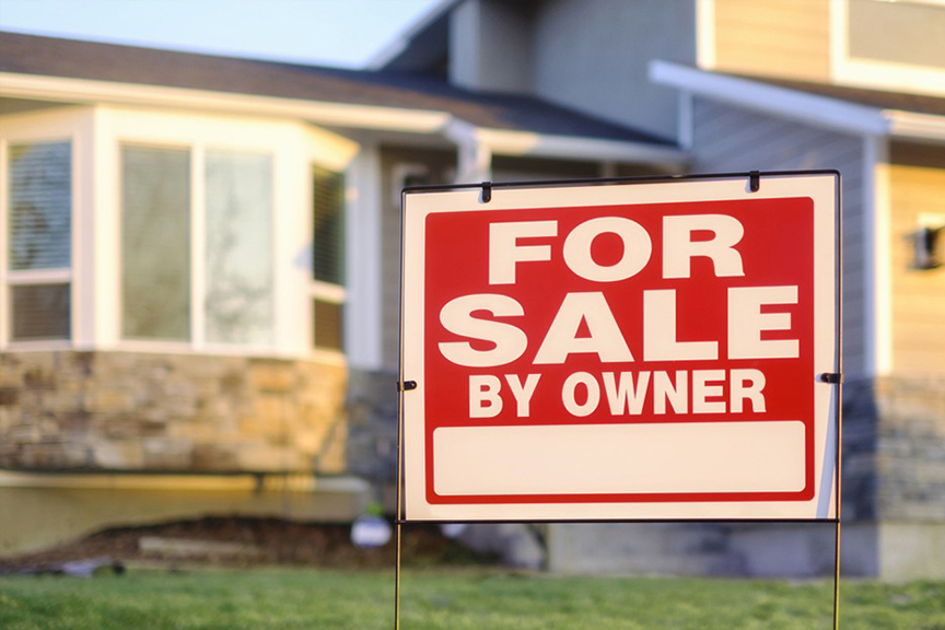 """A red, in focus, """"For Sale By Owner"""" sign standing in front of an out of focus single-family home."""