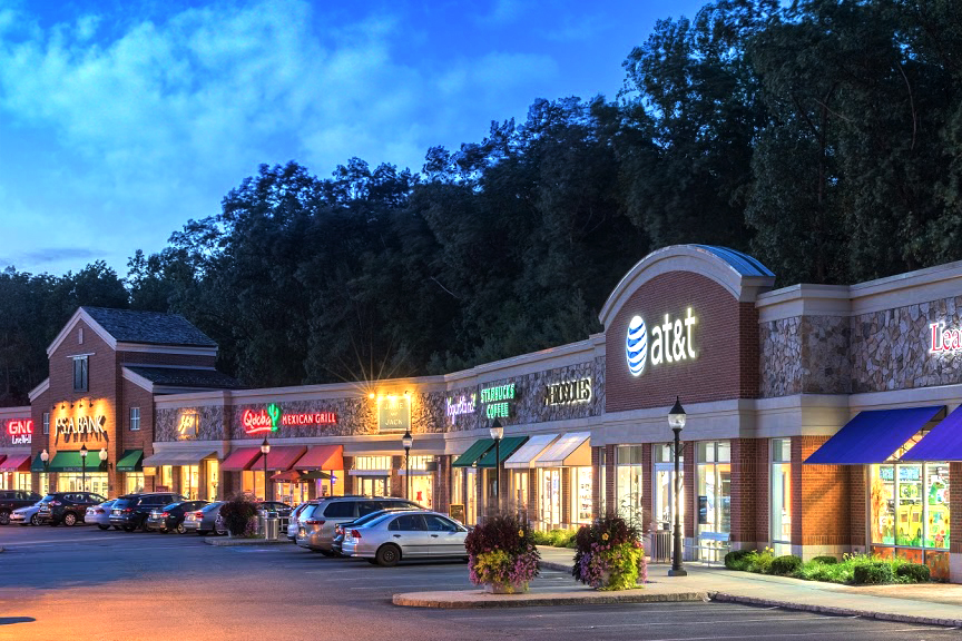 Brightly lit retail strip mall exterior at night; The Shoppes at Union Hill, Denville, NJ.
