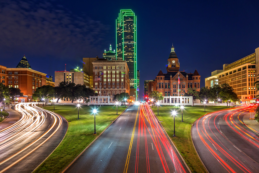 Downtown Dallas skyline, view from above a busy freeway with light trails (long exposure) at night.