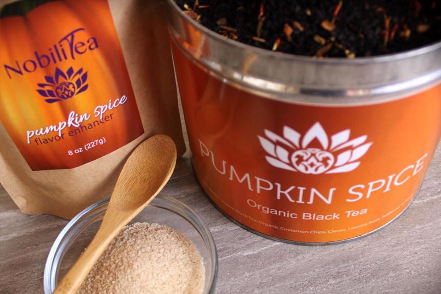 Focus on an open jar of Pumpkin Spice NobiliTea and a bag of Pumpkin Spice flavor enhancer. Orange labels featuring the NobiliTea logo.