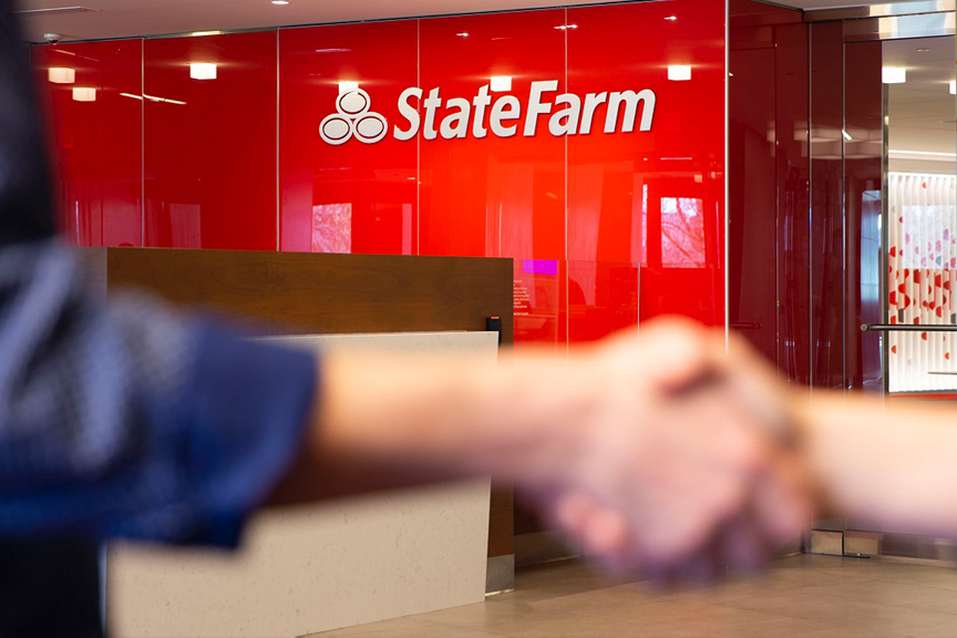 Office interior. Focus on a State Farm logo fashioned to a red, gloss wall. Diminishing focus on two hands shaking in the foreground.