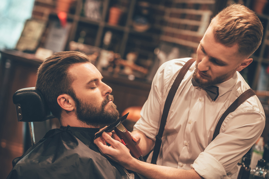 A man having his beard trimmed by a young barber wearing a white button down, suspenders, and a bow tie.