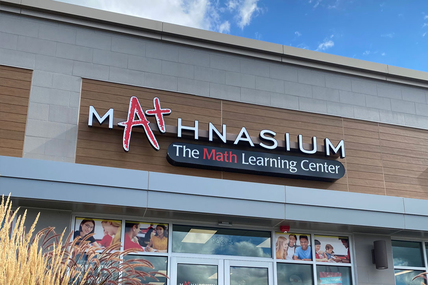 Red and white Mathnasium signage and building exterior against a bright blue sky.
